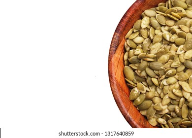 Raw green pumpkin seeds pile without shells inside wooden bowl. Healthy diet food ingredient in round kitchen container studio background.