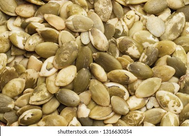 Raw green pumpkin seeds without shell closeup texture. Healthy diet food background.