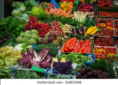 Raw green vegetables/salad/radishes/tomatoes/cabbage/broccoli/ in a market arranged on a stand