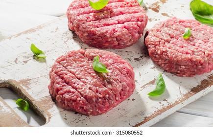 Raw Ground beef Burger steak patties on wooden cutting board. Top view