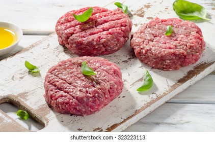 Raw Ground beef Burger steak patties on a white wooden cutting board. Selective focus