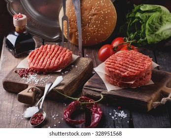 Raw Ground beef meat Burger steak cutlets with seasoning, cheese, tomatoes, salad and bun on vintage wooden boards, black background