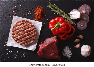 Raw Ground beef meat Burger steak cutlets with ingredients on the board. horizontal view from above closeup