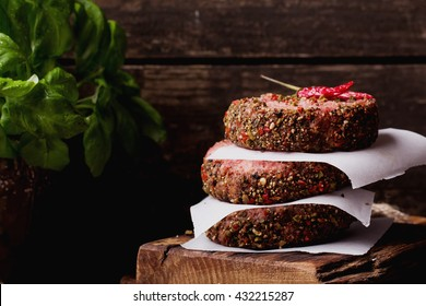 Raw Ground beef meat Burger steak cutlets with chili, basil and seasoning on  rustic wooden board over dark marble background
