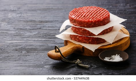 Raw Ground beef meat Burger cutlets and salt on black burned wooden background copy space