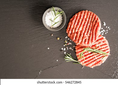 Raw Ground beef meat Burger steak cutlets on a black background stone