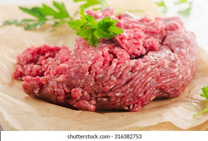 Raw ground beef meat with fresh herbs. Selective focus