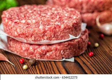 raw ground beef meat hamburger patties on paper, dry pepper and garlic on wooden background