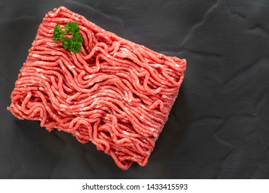 Raw ground beef, top view, on slate.