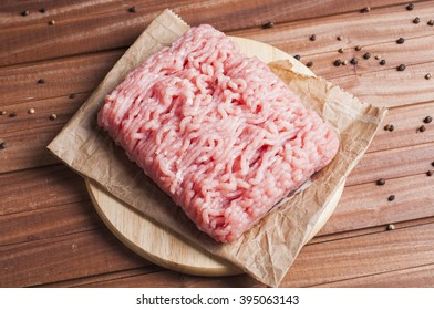 Raw ground turkey meat with spices over wooden background, close-up