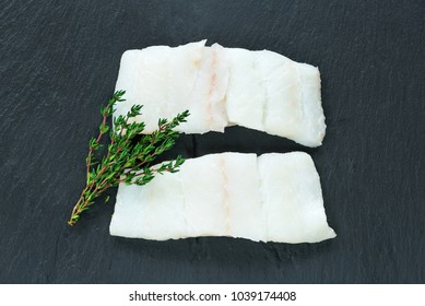 Raw haddock fillets on black board - top view