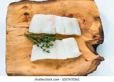 Raw haddock fillets on wooden board - top view