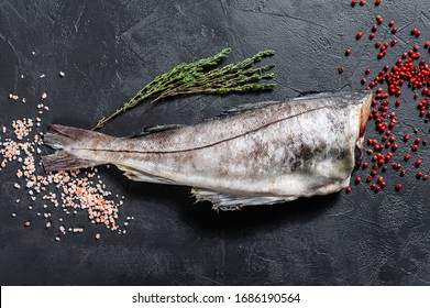 Raw haddock fish without a head. Black background. Top view