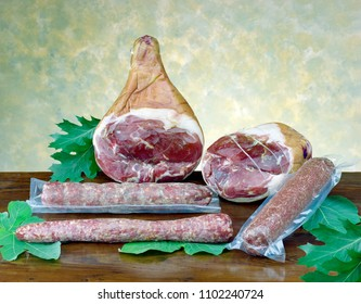 raw ham, vary kind of salami, on wooden table