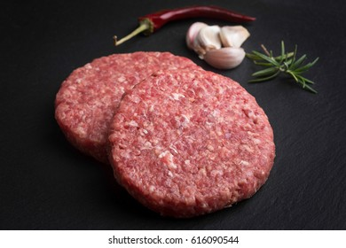 Raw hamburger with spices on a blackboard