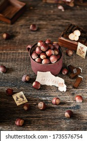 Raw hazelnuts in a metal Cup on a wooden background. Photo in rustic style. Selective focus.