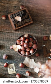 Raw hazelnuts in a metal Cup on a wooden background. There are paper stamps and an inscription in the frame. Rustic style. Top view, selective focus.