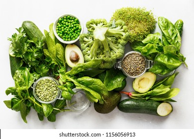 raw healthy food clean eating vegetables grain products source protein vegetarians: cucumber lucerne zucchini spinach basil green peas avocado broccoli lime green lentils concrete background top view