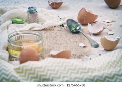 Raw hen egg and empty cracked shells on the top of kitchen table