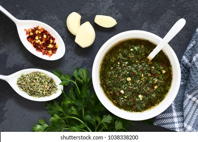 Raw homemade Argentinian green Chimichurri salsa or sauce made of parsley, garlic, oregano, hot pepper, olive oil, vinegar, photographed overhead on slate with natural light (Selective Focus on salsa)