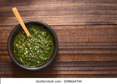 Raw homemade Argentinian green Chimichurri or Chimmichurri salsa or sauce made of parsley, garlic, oregano, hot pepper, olive oil, vinegar, photographed overhead with natural light