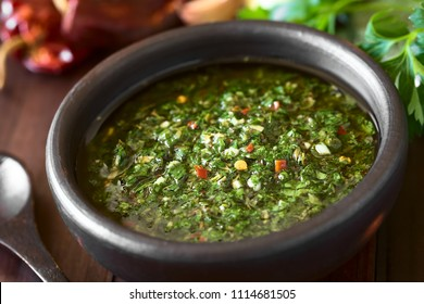 Raw homemade Argentinian green Chimichurri salsa or sauce made of parsley, garlic, oregano, hot pepper, olive oil, vinegar, photographed with natural light (Selective Focus in the middle of the image)