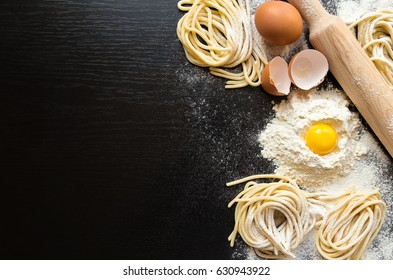 Raw homemade pasta with ingredients on black background. Top view.