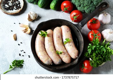 Raw homemade sausages (chicken, turkey) in a pan on a gray background with vegetables. Still life