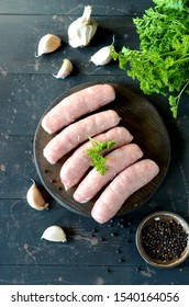 Raw homemade sausages on a wooden cutting board on a dark wooden background