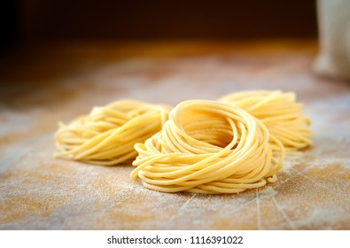 raw homemade spaghetti nest with flour on a wooden table. fresh Italian pasta