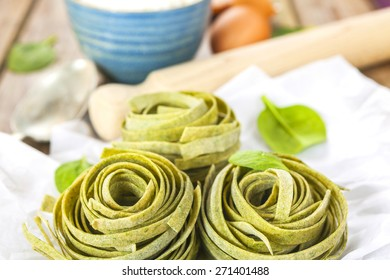 Raw homemade spinach pasta nests with spinach leaves, eggs, bowl of flour, spoon and rolling pin over the rustic wooden table