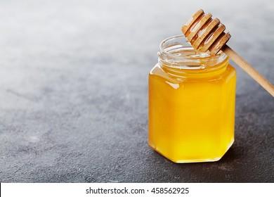 Raw honey in a jar on black table