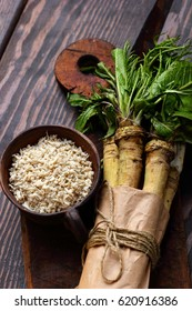 raw horseradish roots on wooden background. horseradish with leaves.Homemade wassabi.Top view