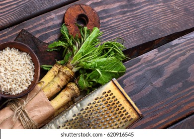 raw horseradish roots on wooden background. horseradish with leaves.Homemade wassabi.Top view.Copy space