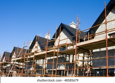raw of houses roofs with scaffolds  in construction site