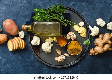 Raw ingredients cooking aloo gobi Indian food on dark stone background