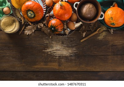 Raw ingredients for cooking pumpkin pie with dry autumn leaves on wooden background with copy space