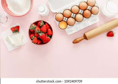 Raw ingredients for making strawberry pie or cake on pink background (eggs, flour, milk, sugar, strawberry) with copy space, top view, flat lay. Bakery background. Recipe for strawberry pie