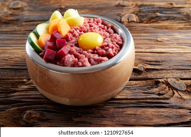 Raw ingredients - minced meat, egg and vegetables in bawl on wooden table viewed from high angle in close-up