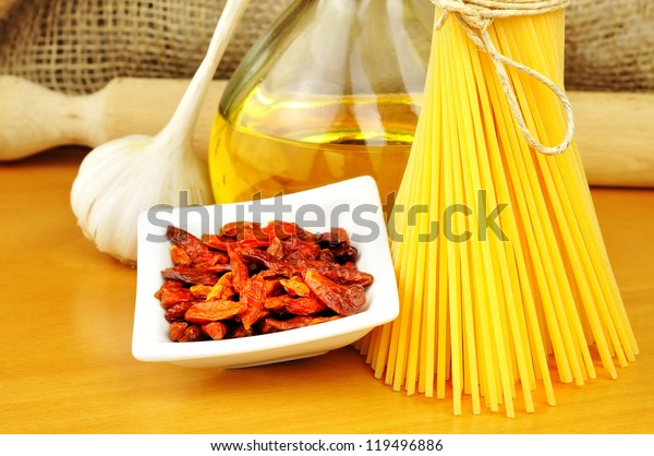 Raw ingredients for spaghetti aglio, olio e peperoncino (garlic, oil, and chili), selective focus