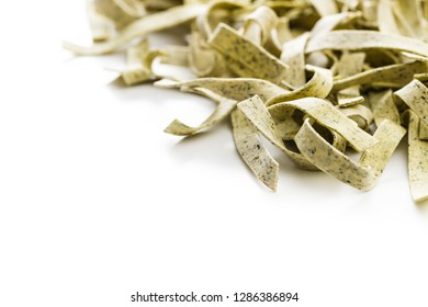 Raw italian pasta. Dry noodles with spinach isolated on white background.