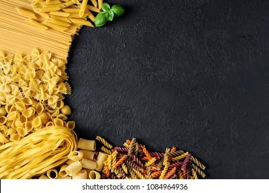 Raw Italian pasta fettuccine, paccheri, farfalle, spaghetti, fusilli, penne, conchiglie on a dark background. Flat lay.