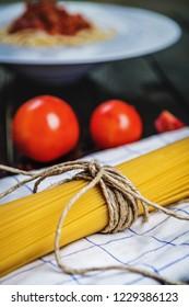 Raw Italian pasta spaghetti and tomatoes on dark wood table