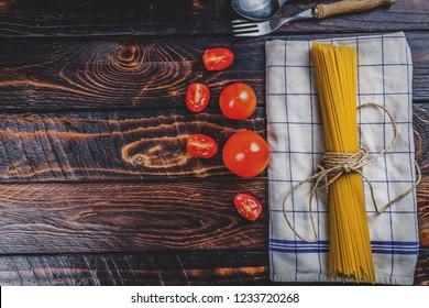 Raw Italian pasta spaghetti and tomatoes on dark wood table top view