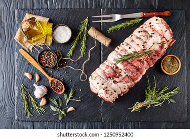 raw italian Porchetta seasoned with sage, rosemary, salt and freshly ground peppercorn, Rolled pork belly on a black stone tray with ingredients, horizontal view from above, flatlay