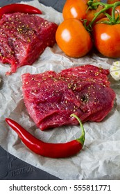 Raw juicy steaks with seasonings, tomatoes, garlic and red chilly peppers.