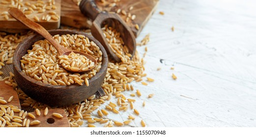 Raw Kamut grain in a wooden bowl with a spoon