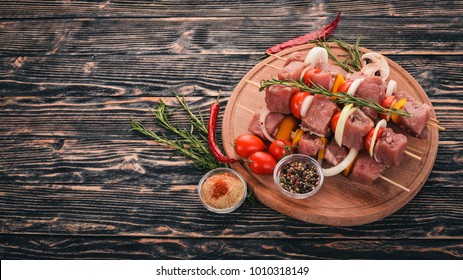 Raw kebab from meat on a wooden background with vegetables. Top view. Free space for text.