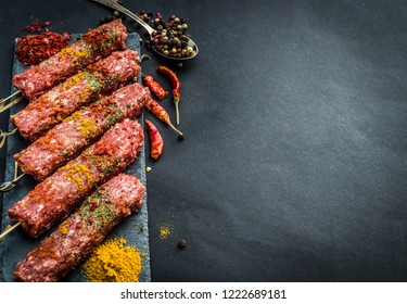 Raw kebab with spices on a black table