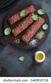 Raw kebabs made of marbled beef meat and seasonings, top view with space on a grey stone background, vertical shot